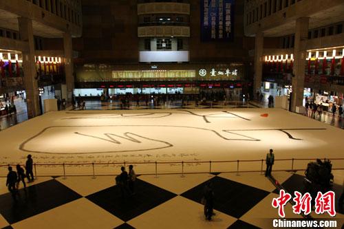 """3月31日,台北市文化局主办的第8届""""汉字文化节""""开幕,图为书法家洪启嵩今天持巨笔,在台北车站1楼售票大厅写下27乘38米的超级大""""龙""""字,为活动揭开序幕。"""