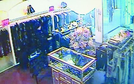 监控录像显示女子在划衣服的画面 记者 龙在全 翻拍