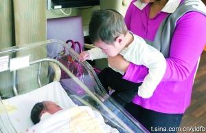 李嘉欣/李嘉欣姐姐的儿子望着睡觉的小表弟。