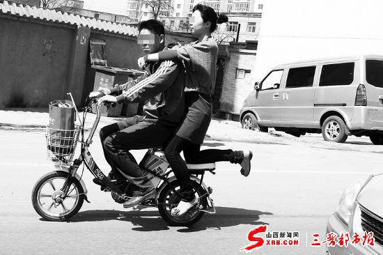 """一位女士以高难度动作""""坐""""在自行车后座上,穿行在车流中,十分危险."""