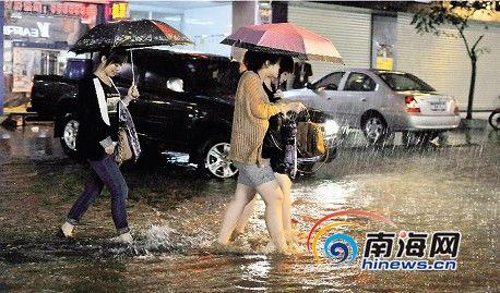 4月7日晚9时,在海口市蓝天路,市民走在积水较深的街道上。当天,上午11时,海口市气象台发布暴雨橙色预警信号。本报记者宋国强摄