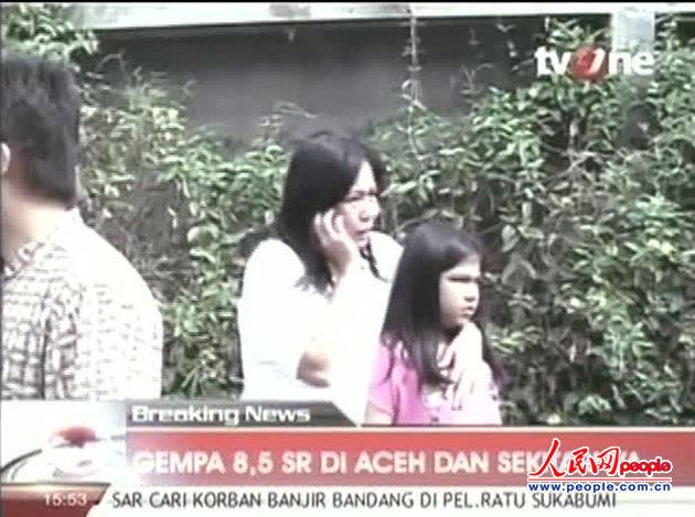 在印尼电视一台的画面中,一位女士一边搂着一个女孩,一边用手机打电话。在印尼海域发生强震之后,附近的居民纷纷跑出楼房,逃往更高的地方避难。