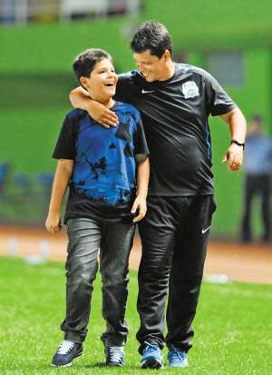 广州富力队主教练法里亚斯(右)赛后离场时和他的儿子谈笑。