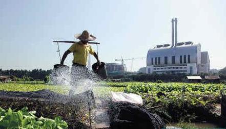 王飞 李坑/农民正在靠近李坑垃圾处理厂的田里浇地。记者王飞/摄资料图片