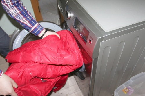 将羽绒服放入洗衣机内筒中,并放入适当洗涤剂