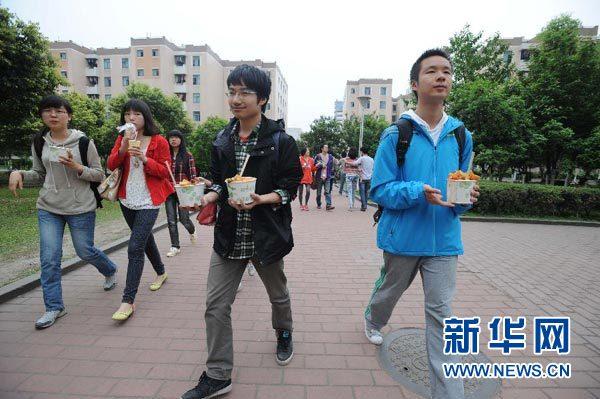 4月19日,四川大学江安校区内,学生们从校食堂打回午饭走向宿舍.