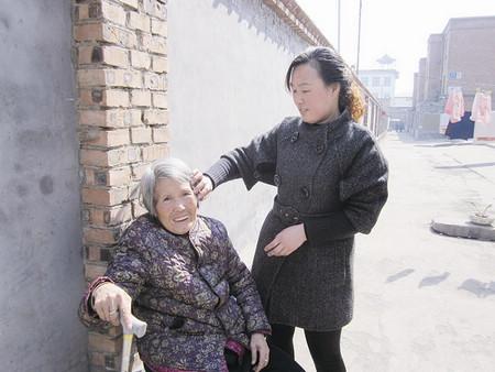 刘慧兰为郑玉梅老人整理头发图片
