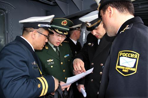 """4月21日,边检警官在""""瓦良格""""号导弹巡洋舰上为官兵办理入境检查手续。"""