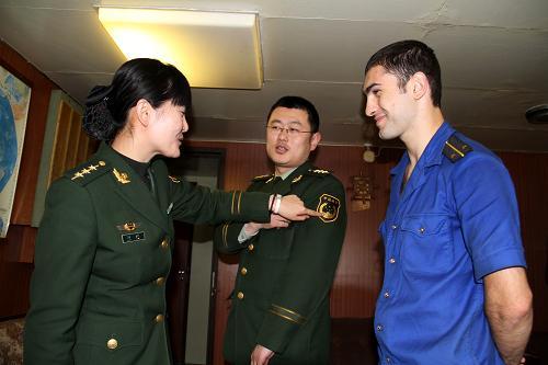 """4月21日,""""佩琴加""""号上,边检警官高艳(左一)在向穆拉特中尉介绍中国军服及军衔。"""