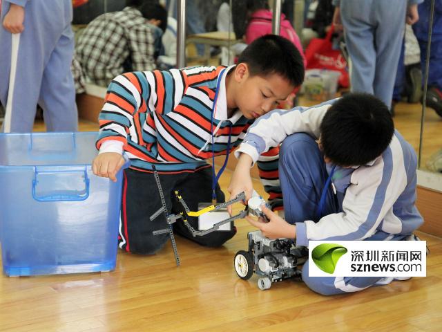 深圳/两位小选手正认真组装机器人