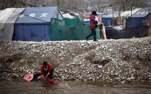 4月23日,青海玉树,藏族灾民在帐篷村附近洗衣服。