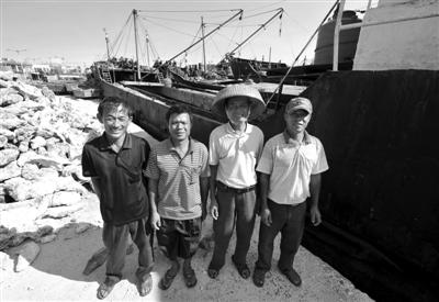 """15日,""""琼・琼海09099船""""的4名船员返航后在渔船前合影。"""