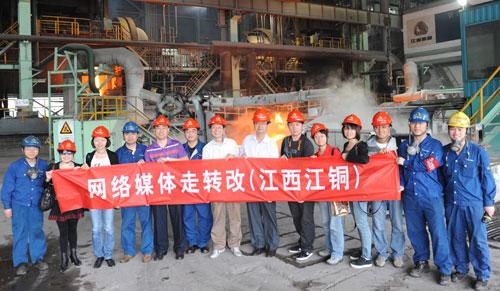 """""""网络媒体走转改""""联合报道组成员与江铜集团工作人员在合影,身后是热火朝天的阳极铜生产车间。"""