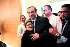 6日,在希腊首都雅典新民主党总部,支持者拥抱得票率第一的新民主党领导人安东尼斯·萨马拉斯。 新华/法新