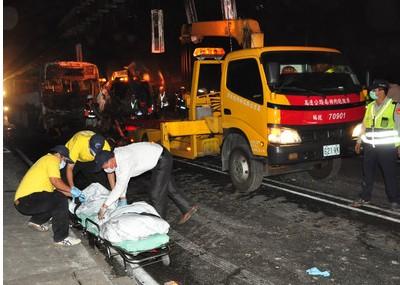 """图4:车祸共造成2死及20多人受伤。消防人员事后将焦黑的尸体运出。来源:台湾""""中央社"""""""