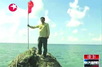 记者登上黄岩岛主礁并插上国旗