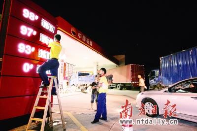 今天凌晨零时,广州新港西路某加油站等待加油的司机,在一旁观看油站员工更换汽油报价板上的汽油价格。吴伟洪