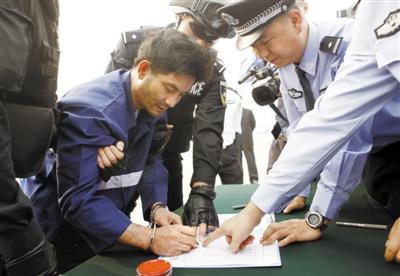 在首都机场当场在《逮捕证》上签字。 新华社发