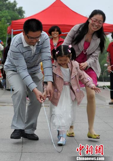 孩子和家长一起滚铁环。寒单摄