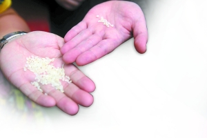 一年收费两万多这样的高价幼儿园会给孩子吃劣质米吗 昨日,伊顿慧智幼儿园内,家长仔细查看封存在大桶内的大米。本版图/重庆晨报记者 黄宇 摄