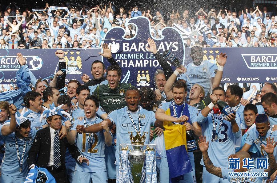 5月14日,曼城队球员在曼彻斯特市政厅前与球迷共同庆祝夺得联赛冠军。当日,首次夺得英格兰足球超级联赛冠军的曼城队举行全城巡游庆典。新华社/路透