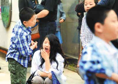 五月十三日,北京八中进行第十九届少儿班招生测试,一大早不到七时,上百名母亲就带着孩子赶到学校,等待进入考场。一名还没睡醒的年轻母亲蹲在地上打起了哈欠。贾同军摄