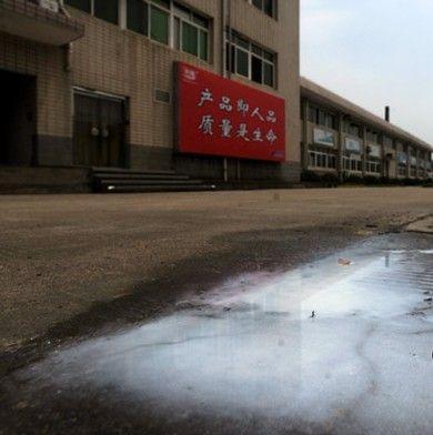 昨日,光明乳业厂门口被倾倒的牛奶。图/记者邵骁歆