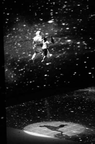"""演出中,一位宇航员牵着小朋友在""""太空""""漫步,在特效帮助下,飘在空中的演员与环形屏幕完美融为一体 摄/记者林晖"""