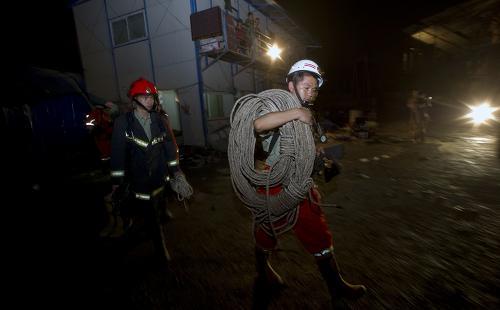 5月20日凌晨,搜救人员从发生事故的隧道口附近走过。新华社记者 李尕 摄