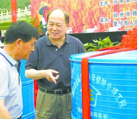 苗永清_省粮食局局长苗永清右和农民交流粮仓的使用方法