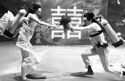 李哲/5月19日,新郎李哲(右)在水下向新娘献花。