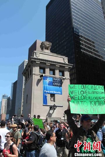 当地时间5月18日,数千示威者冲击北约峰会举办地芝加哥,警察防不胜防。图为示威者撕毁了芝加哥交通要道上的北约峰会标语牌,并占据道路示威,使芝加哥交通陷入瘫痪。中新社发 李洋 摄