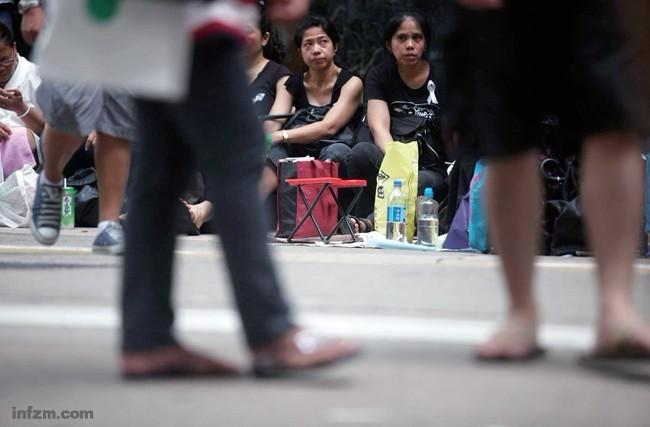 黄岩岛对峙,让在中国大陆务工的菲佣似乎也处于一种莫名的尴尬之中。一如菲律宾人质事件之后,香港工作的菲佣。图为香港举行声讨追思的游行队伍边,正在聚会的菲佣。 (南方周末记者 王轶庶/图)