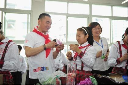 李厚霖先生与重庆市合川区特殊教育学校的聋哑孩子共同制作丝网花。
