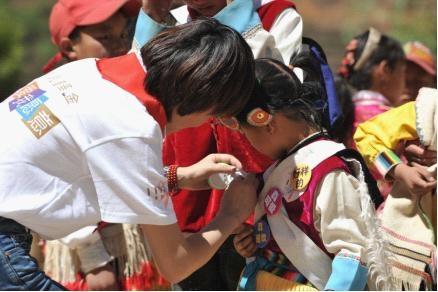 I Do基金工作人员为游戏闯关成功的达祖希望小学的少数民族小姑娘佩戴爱心勋章。