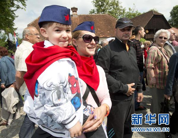 """5月26日,在克罗地亚库姆罗韦茨村,一对母子戴着""""铁托帽""""和红领巾,参加纪念前南斯拉夫领导人铁托诞辰120周年活动。"""