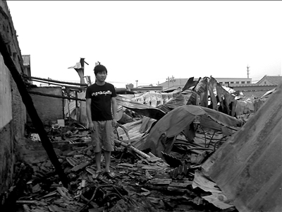 小彭脚下是他被震塌的房子。