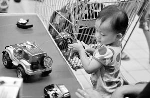 陆明杰/海珠区一家大型超市里,父母带着小孩在选购玩具车。信息时报...