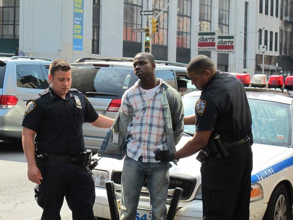 两名警员将冲入华人店中闹事的非裔男子铐上手铐,送交法办。美国《侨报》/苏夏竹 摄