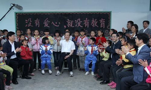5月25日,在古丈县双溪乡中心完全小学音乐教室,温家宝与教师、留守儿童和家长座谈。新华社记者 庞兴雷 摄