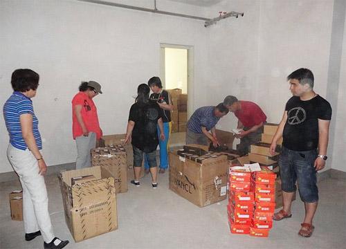 """""""思源•焦点""""公益基金的工作人员和志愿者一起将922双鞋打包"""