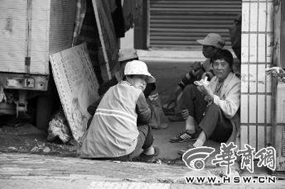 """5月26日下午,汉中市4名环卫工人坐在阴凉处""""享受""""晚餐白面馍馍 本报记者 陈兴王 摄"""
