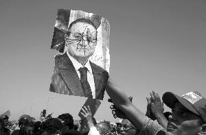 2日,在埃及开罗警察学院外,人们举着丑化前总统穆巴拉克的画像 新华社/路透