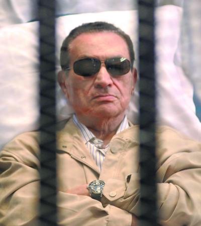 现年84岁的穆巴拉克戴着墨镜在铁笼里受审。