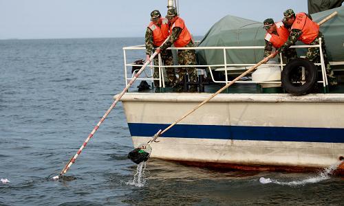 6月2日,辽宁海警二支队官兵在丹东黄海海域用网抄清理海面上漂浮的垃圾。新华社发(桂子云 摄)