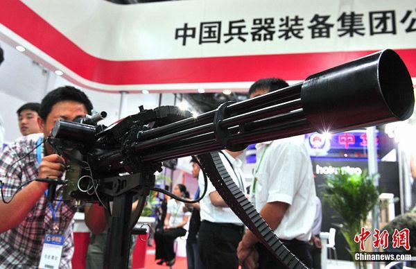 """5月23日,在北京国家会议中心举办的""""第六届中国国际警用装备博览会""""热闹非凡。中国兵器装备集团下属部门生产的CS/LM12型7.62毫米转管机枪最高射频为每分钟6000发,常用射频每分钟2500发,以小于或等于2.3千瓦的电力,驱动枪管转轮旋转。中新社发 邹宪 摄"""