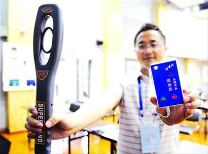 6月6日,在华东模范中学考点内,工作人员在展示金属探测棒和无线耳机探测器。