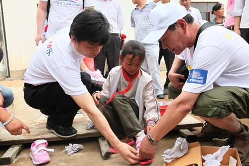 崔永元(左)帮孩子穿鞋.