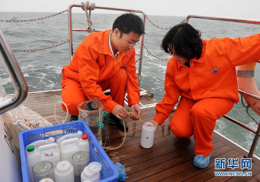 青岛/6月7日,青岛海洋局工作人员在浒苔出现海域抽取监测水样。