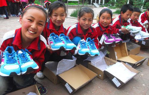 青海省贵德县河东乡明德小学的孩子领到运动鞋